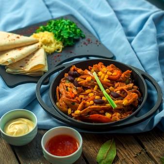Zijaanzicht kip fajitos in een pan met bonen pitabroodje en sauzen