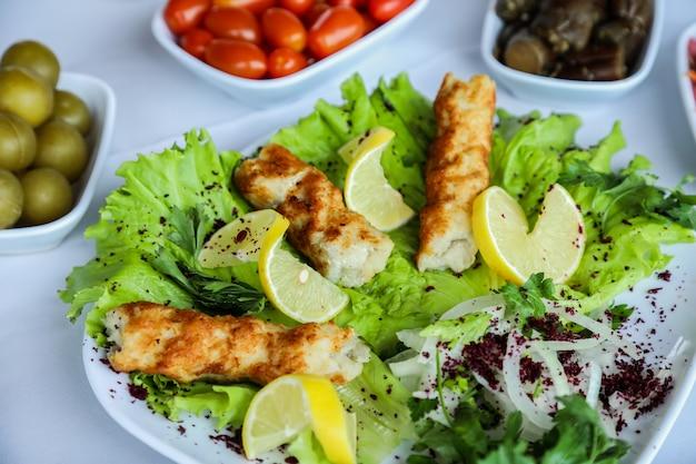 Zijaanzicht kip lula kebab met plakjes citroen uien en op een sla blad op een plaat