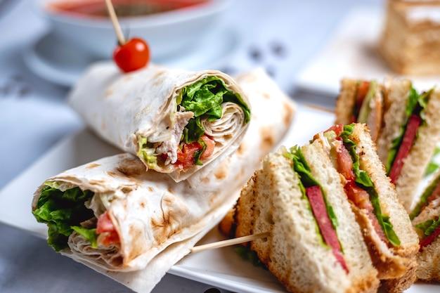 Zijaanzicht kip roll gegrilde kipfilet met sla greens mayo verpakt in tortilla en club sandwich op tafel