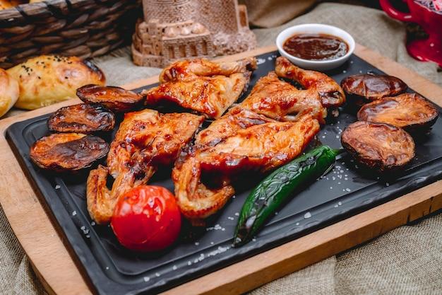 Zijaanzicht kip tabaka met gegrilde tomaat aardappel hete groene paprika en saus op een dienblad