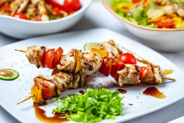 Zijaanzicht kipspiesjes gegrilde kip met tomaten paprika saus en sla op een bord