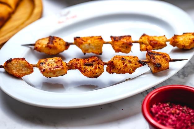 Zijaanzicht kipspiesjes gegrilde kipfilet met zout en peper op een plaat