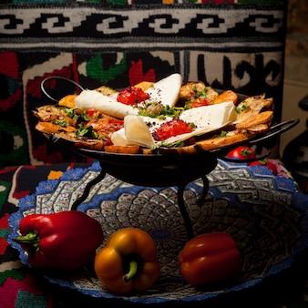 Zijaanzicht kipzak met gebakken aardappelen en paprika en lavash