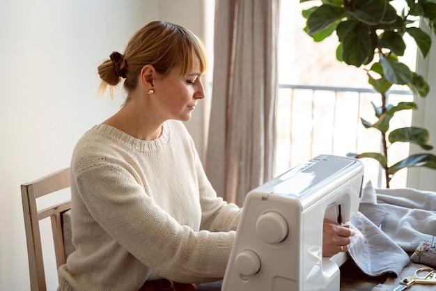 Zijaanzicht kleermaker vrouw met behulp van naaimachine