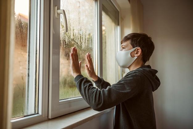 Zijaanzicht kleine jongen met gezichtsmasker kijkt door het raam
