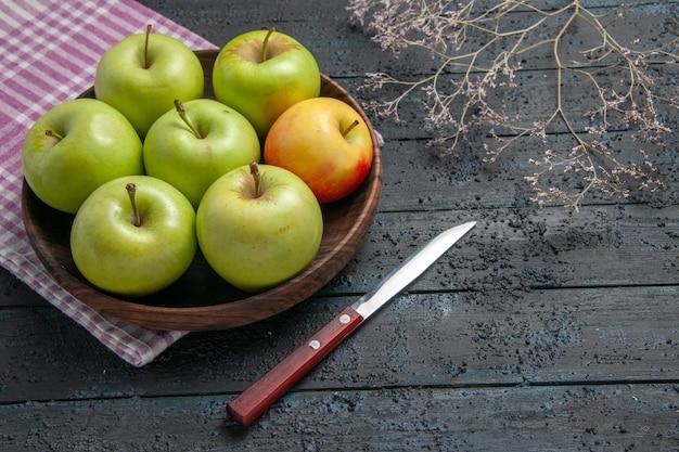 Zijaanzicht klinker van appels kom van zeven groen-geel-rode appels op geruit tafelkleed naast mes en takken