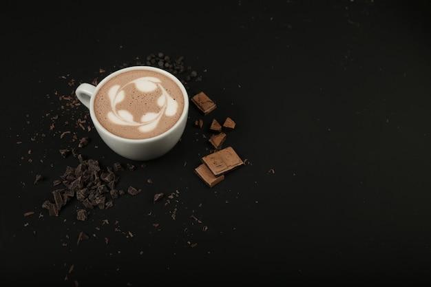Zijaanzicht kopje cappuccino met chocolade op zwarte tafel