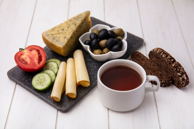Zijaanzicht kopje thee met gerookte kazen met olijven, tomaat, komkommer en sneetjes zwart brood op een witte achtergrond
