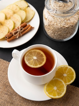 Zijaanzicht kopje thee met plakjes citroen en appel segmenten met kaneel op een plaat