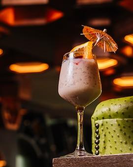 Zijaanzicht koude fruitcocktail met yoghurt en sinaasappel in het glas Gratis Foto