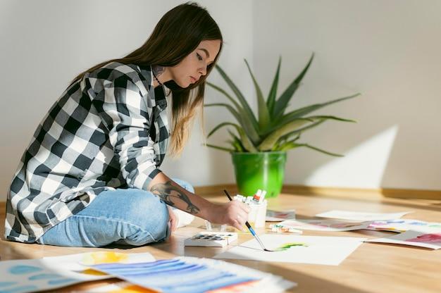 Zijaanzicht kunstenaar met haar schilderijen en aloë vera