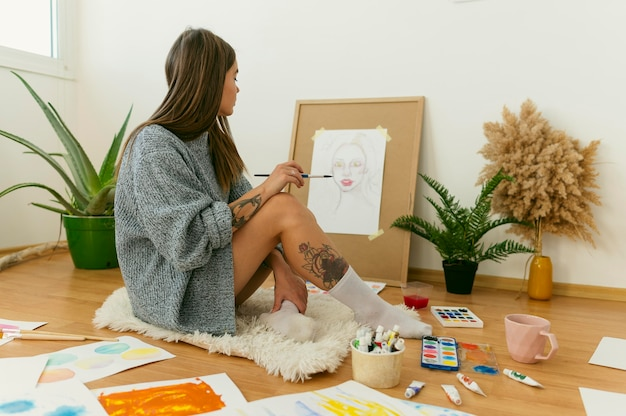 Zijaanzicht kunstenaar zittend op de vloer en schilderen op canvas