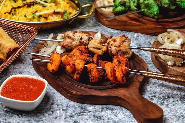 Zijaanzicht lams kebab met garnalen gegrilde ui en saus op een bord