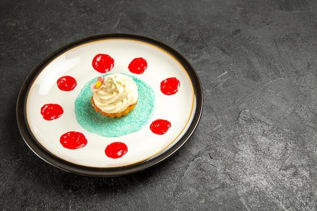 Zijaanzicht lekker eten op het witte bord een smakelijke cupcake met sauzen op het donkere oppervlak
