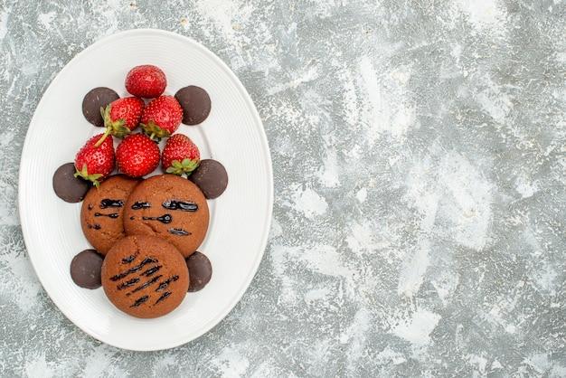 Zijaanzicht linksboven chocoladekoekjes aardbeien en ronde chocolaatjes op het witte ovale bord op de grijswitte ondergrond