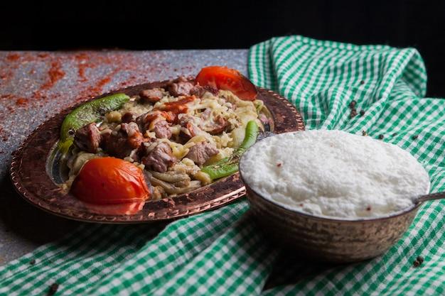 Zijaanzicht lule kebab gemengde auberginesalade met tomaat en papier en ayran