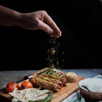 Zijaanzicht lule kebab met tomaat en papier en ayran en hand voegt kruiden toe in serveerplank
