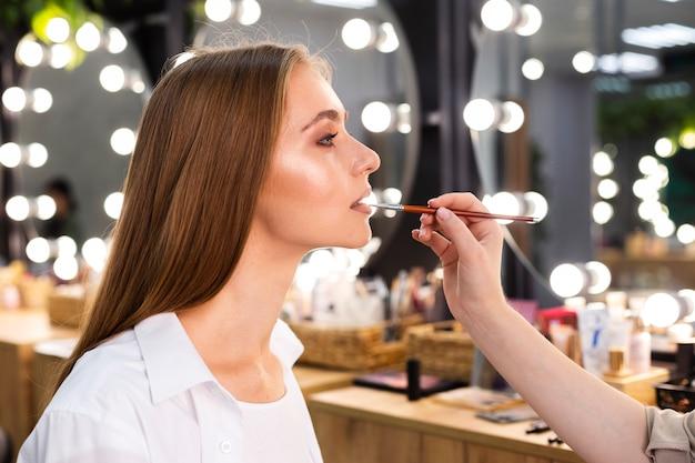 Zijaanzicht make-up artiest lippenstift op lachende vrouw met borstel toe te passen
