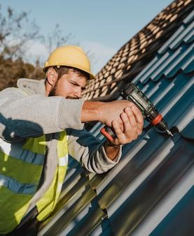 Zijaanzicht man aan het werk op dak met een boormachine