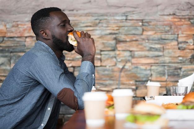 Zijaanzicht man hamburger eten