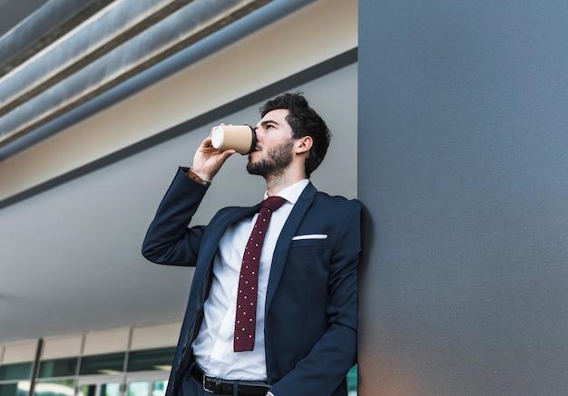Zijaanzicht man in pak koffie drinken