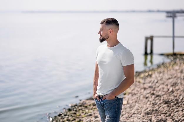 Zijaanzicht man kijkend naar de zee