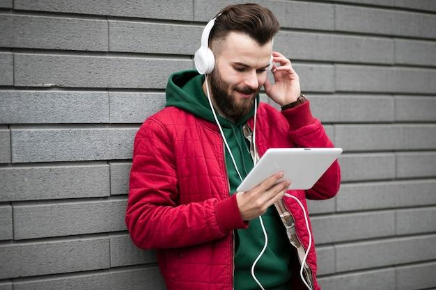 Zijaanzicht man met koptelefoon en tablet