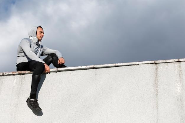 Zijaanzicht man zittend op een muur en wegkijken