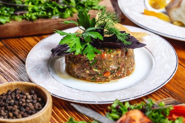 Zijaanzicht mangal salade geroosterde aubergine paprika ui tomaten greens en zwarte peper op tafel