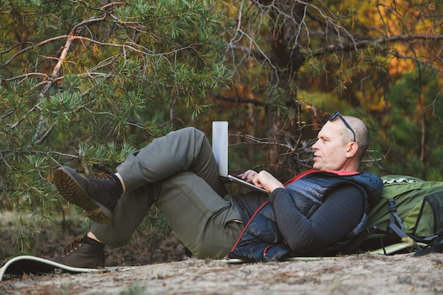 Zijaanzicht, mannelijke wandelaar liggend op de rug, leunend op rugzak, met laptopcomputer, typen, bloggen, browsen in het bos