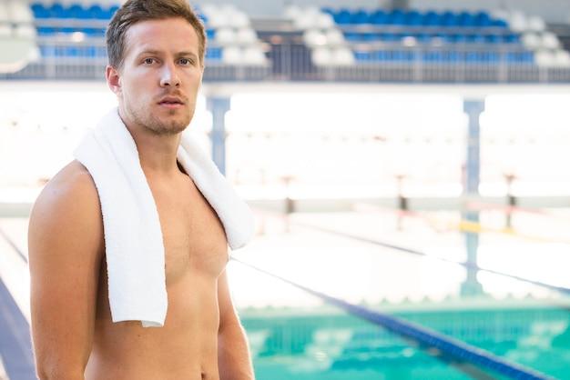 Zijaanzicht mannelijke zwemmer met handdoek bij bassin