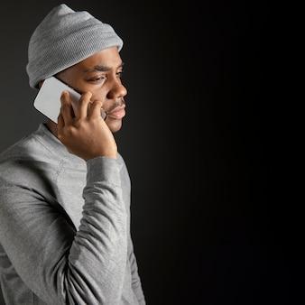 Zijaanzicht mannetje dat glb draagt dat op telefoon spreekt