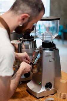 Zijaanzicht mannetje dat koffie voorbereidt