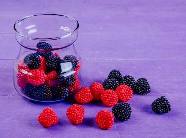 Zijaanzicht marmelade in de vorm van frambozen en bramen in een pot op een paarse achtergrond