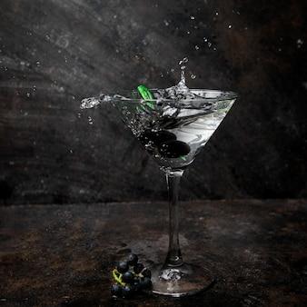 Zijaanzicht martini in een glas met olijven