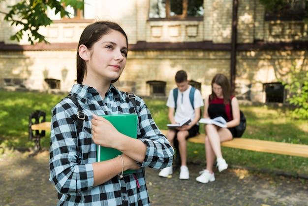 Zijaanzicht medium shot van dromerige highschool meisje bedrijf notebook