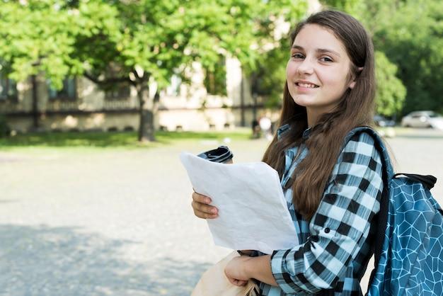 Zijaanzicht medium shot van school meisje bedrijf notities