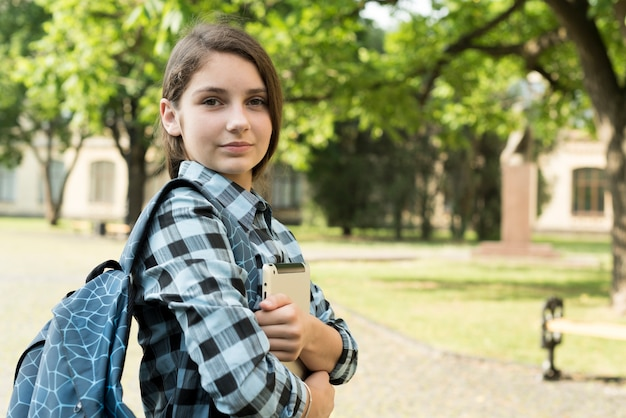 Zijaanzicht medium shot van vertrouwen schoolmeisje bedrijfstablet