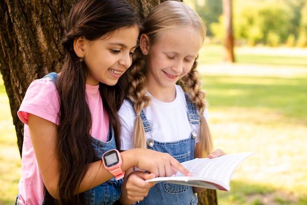Zijaanzicht meisjes naast boom lezen