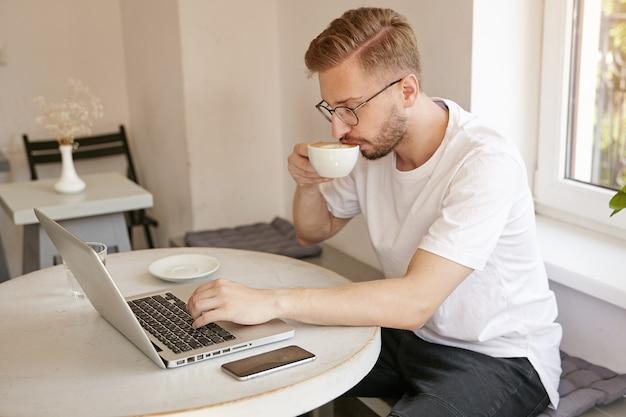 Zijaanzicht met bebaarde mooie man in wit t-shirt, koffie drinken en op afstand werken met laptop in openbare ruimte, kleine pauze maken