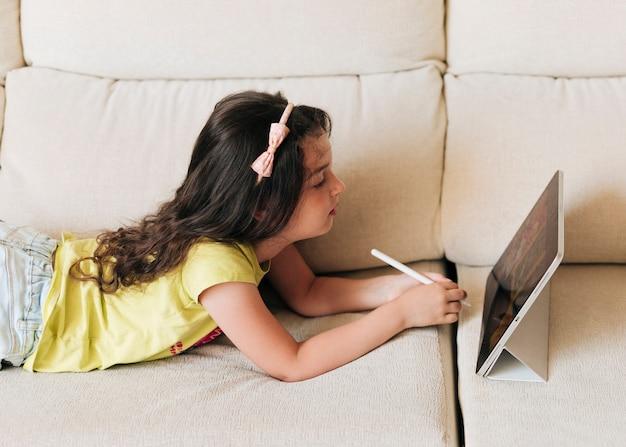 Zijaanzicht met pen die haar tablet bekijkt