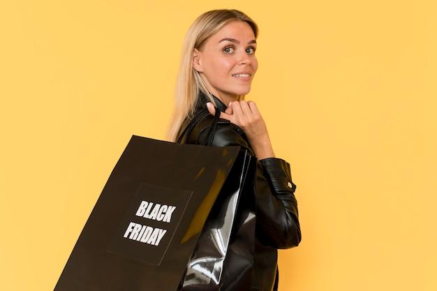 Zijaanzicht mode dame draagt zwarte kleding met zwarte vrijdag tas