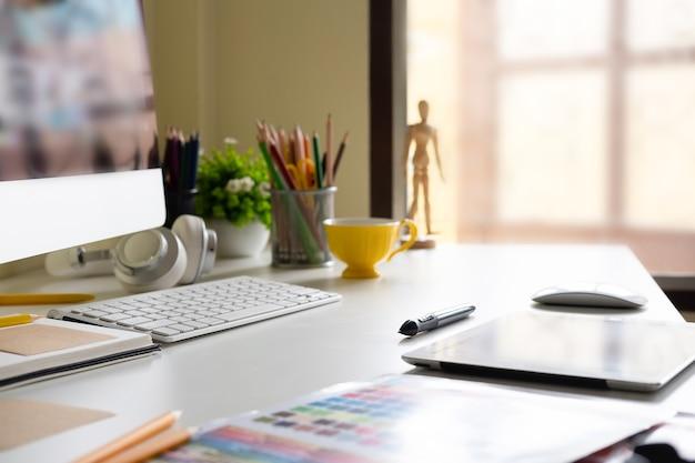 Zijaanzicht moderne bureauwerkplaats met digitale tablet, blocnote, kleurrijke potloden, computer