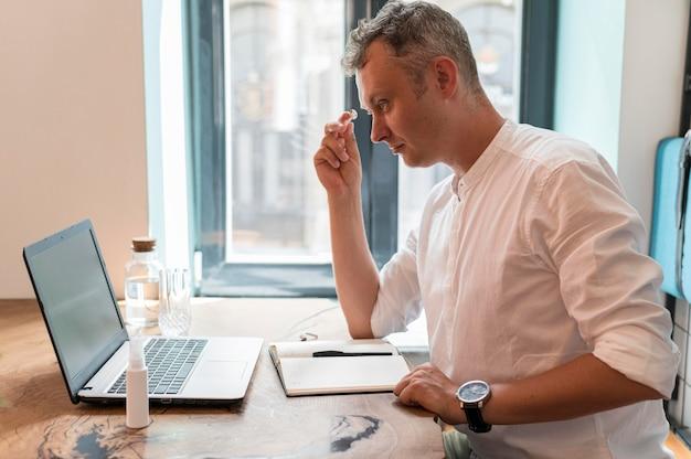 Zijaanzicht moderne man aan het werk op laptop