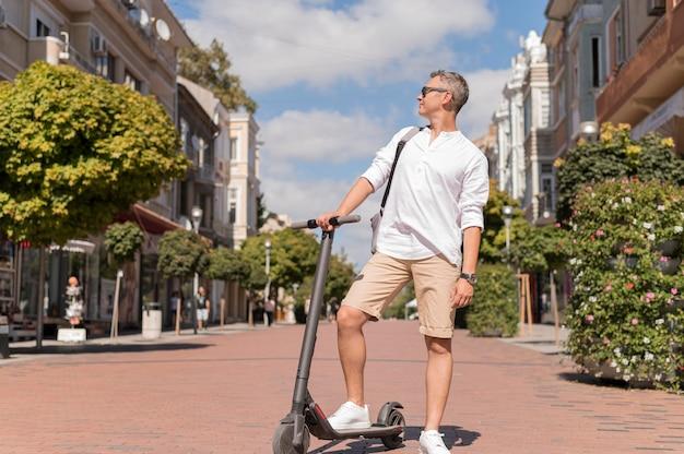 Zijaanzicht moderne man op scooter