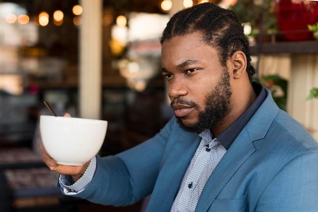 Zijaanzicht moderne man zijn koffie drinken in een restaurant
