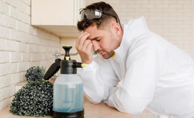 Zijaanzicht moe man met ontsmettingsmiddel