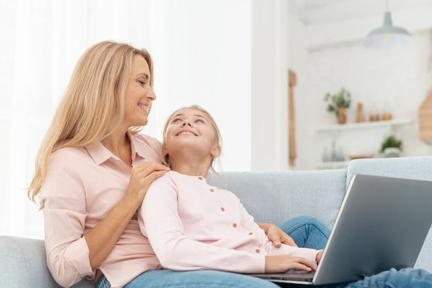 Zijaanzicht moeder en dochter die op laptop werkt