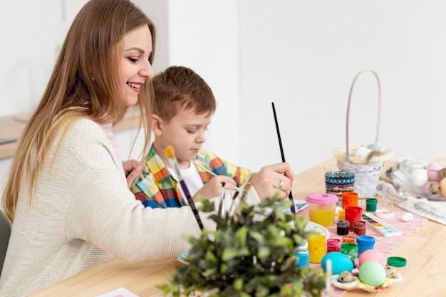 Zijaanzicht moeder en zoon schilderen eieren