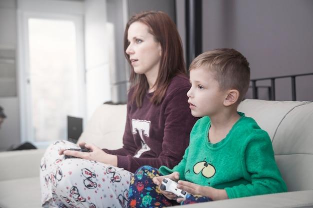 Zijaanzicht moeder en zoon spelen van videogames